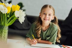 Portrait of cute little child drawing with colored pencils and smiling at camera. At home royalty free stock images