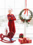 Little child in holiday christmas white and red interior Stock Photos