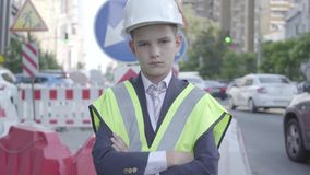 Portrait cute little confidient boy wearing business suit and safety equipment and constructor helmet standing on a busy stock video