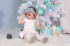 Portrait of cute little crying Princess girl in beautiful dress and striped hat sitting in studio decorated in christmas theme stock photos