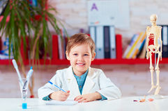 Portrait of cute little doctor writing notes in lab Stock Photography