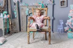 Portrait of a cute little european blond princess girl in a beautiful dress sitting on a vintage chair in a studio decorated in stock photo