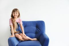 Portrait of cute little girl on armchair. Against white wall Stock Photo