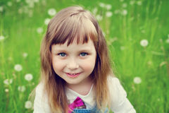 Portrait of cute little girl with beautiful smile and blue eyes sitting on the flower meadow, happy childhood. Concept, child having fun, toned image Royalty Free Stock Image