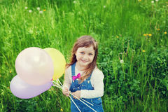 Portrait of cute little girl with beautiful smile holding toy balloons in hand on the flower meadow, happy childhood Royalty Free Stock Image