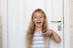 Portrait of cute little girl with blonde hair which cleaning tooth with brush and toothpaste in bathroom stock image