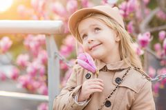 Portrait of cute little girl with blonde hair which holding hand pink flower of magnolia. Spring season stock image