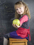Portrait of cute little girl with book and green apple near blackboard Stock Photo