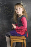 Portrait of cute little girl with book and green apple near blackboard Stock Photography