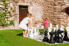 Portrait of  cute little girl and boy playing chess. Two little kids playing giant chess outdoors Royalty Free Stock Photos