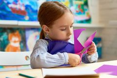 Cute Girl Cutting Out Paper Heart in Craft Class Stock Image