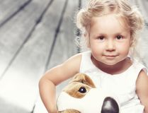 Portrait of a cute little girl in casual dress sitting with a plush toy in studio. stock photography
