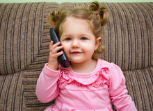 Portrait of a cute little girl on chair talking on the phone Royalty Free Stock Photography