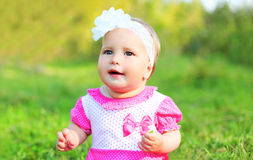 Portrait cute little girl child sitting on grass in summer Stock Photography