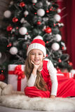 Portrait of a cute little girl on a christmas tree background. Stock Photo