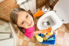 Portrait of cute little girl cleaning toilet with brush Royalty Free Stock Photo