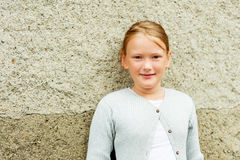 Portrait of a cute little girl. Close up portrait of a cute little girl of 8-9 years old, wearing grey  knitted jacket Stock Photos