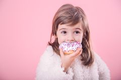 Portrait of cute little girl with donut. Portrait of a cute little girl eating a donut isolated on pink background royalty free stock photo