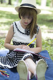 Portrait of a cute little girl in a dress with a hat while sitti. Ng on a blanket on the grass and draws in his notebook. She draws with wooden crayons Royalty Free Stock Photos