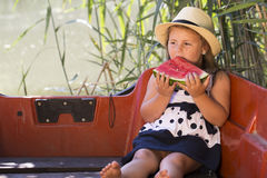 Portrait of a cute little girl in a dress with a hat while sitti. Ng in a boat on a lake and eating a juicy watermelon. She loves spending time in nature Stock Photo