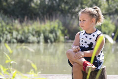 Portrait of a cute little girl in a dress while sitting next to. The river. She plays on a beautiful sunny summer day. Child happiness, joy, growing up. Copy Royalty Free Stock Photo