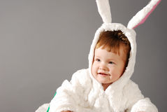 Portrait of a cute little girl dressed in Easter bunny suit. On a gray background Stock Photography