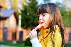 Portrait of cute little girl eating big lollipop Stock Photos