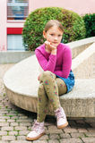 Portrait of a cute little girl. Fashion portrait of a cute little girl in a city, wearing pink shoes, t-shirt, denim skirt and green tights Royalty Free Stock Photography