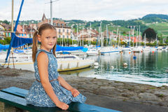 Portrait of a cute little girl. Fashion portrait of a cute little girl sitting on a bench by the lake, wearing blue dress Royalty Free Stock Images