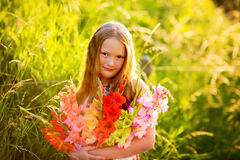 Portrait of a cute little girl. Golden hour portrait of a cute little girl of 8 years old, holding colorful gladiolas flowers Royalty Free Stock Photo