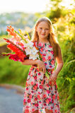 Portrait of a cute little girl. Golden hour portrait of a cute little girl of 8 years old, holding colorful gladiolas flowers, vertical image Stock Photo