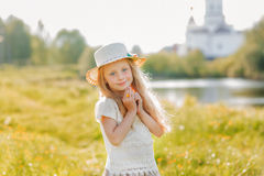 Portrait of a cute little girl in a hat on a background of a church on a summer day Stock Photos