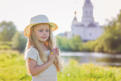 Portrait of a cute little girl in a hat on a background of a church on a summer day Stock Photo