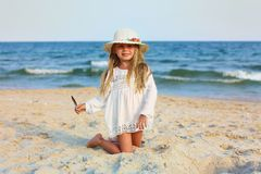 Portrait of a cute little girl in a hat on the beach stock photo