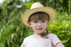 Portrait of Cute little girl with hat in the garden Royalty Free Stock Image