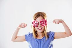 Portrait of a cute little girl having fun with two lollipops, covering her yes with them. Stock Photo