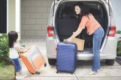 Little girl and mother preparing for holiday. Portrait of cute little girl with her mother preparing suitcase into a car for holiday, shot in the house garage Royalty Free Stock Photos