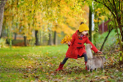 Portrait of a cute little girl and her pet cat on beautiful autumn day Royalty Free Stock Photos