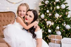 Cute little girl and his mother in white dresses sitting in deco royalty free stock photos