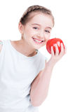 Portrait of cute little girl holding an apple. Royalty Free Stock Photography