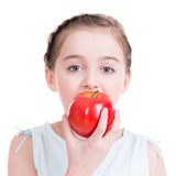 Portrait of cute little girl holding an apple. Stock Photo