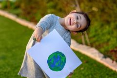 Portrait of the cute little girl holding the drawing earth globe. Child drawng a picture of earth. royalty free stock image