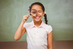 Portrait of cute little girl holding magnifying glass Stock Photo