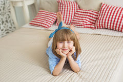 Portrait of cute little girl lies on a bed Stock Images