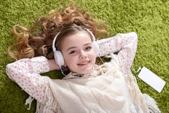 Portrait of a cute little girl listening music stock images