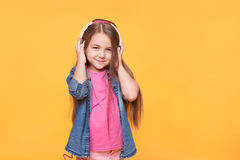 Portrait of cute little girl listening to music over yellow. Background Royalty Free Stock Photo