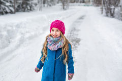 Portrait of a cute little girl with long blond hair, dressed in a blue coat and a pink hat in the winter forest Stock Image
