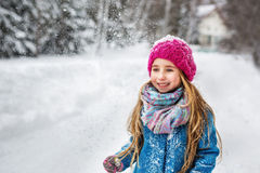 Portrait of a cute little girl with long blond hair, dressed in a blue coat and a pink hat in the winter forest Royalty Free Stock Photography