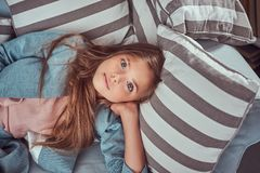 Portrait of a cute little girl with long brown hair and piercing glance, looking at a camera, lying on a sofa at home royalty free stock photo