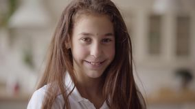 Portrait of cute little girl looking at camera smiling happily. Carefree childhood. Little emotional girl at home. Real stock video